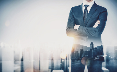 Young businessman wearing modern suit and standing with his arms crossed. Double exposure.