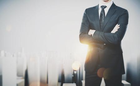 Foto van zakenman draagt modern pak en staat met zijn armen gekruist. Stockfoto