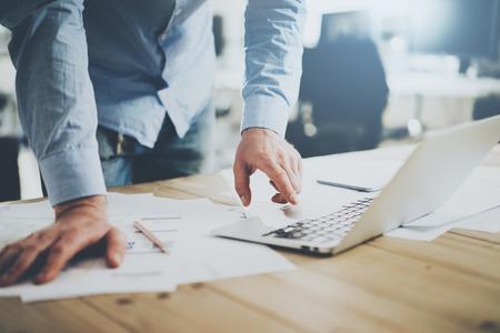 Biznesmen pracuje w nowoczesnym studiu cretive. Korzystanie ogólny projekt laptopa. Projekt architektoniczny na stole. Zdjęcie Seryjne