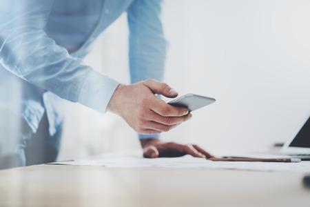 Foto von generischen Design Smartphone holding in Geschäftsmann Händen. Unscharfen Hintergrund.