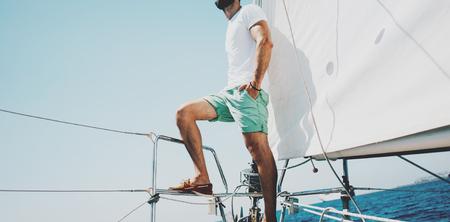 Faible angle de vue d'un jeune homme barbu debout sur le yacht. Banque d'images