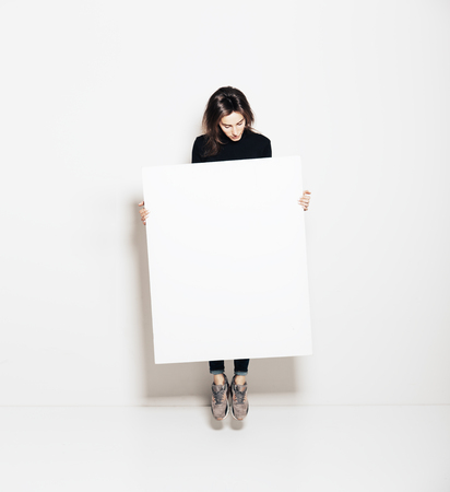 Photo of girl jumping in modern gallery and looking at the blank white canvas. Horizontal
