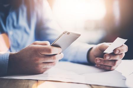 Geschäftskonzept. Unternehmer, die Hand weiß Visitenkarte und Foto-Smartphone zu machen. Neue Arbeits Projekt auf dem Tisch. Horizontal Mockup.