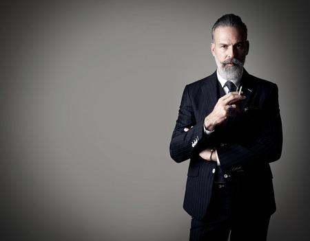 トレンディな身に着けている喫煙紳士の肖像画は、スーツし、空の壁に対して立ちます。