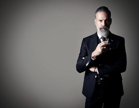Portret szlachcica palenia sobie modny garnitur i stoi na tle pustej ściany.