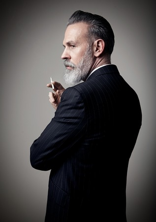 Portrait of adult businessman wearing trendy suit and holding cigarette against the empty wall. Stock Photo