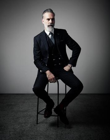 Portrait der erwachsenen Geschäftsmann trendy Anzug und Studio auf dem Stuhl vor dem leeren Wand sitzt.