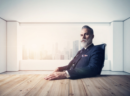 Portrait of adult businessman wearing trendy suit and sitting modern loft on leather chair against the panoramic window with city view. Stockfoto