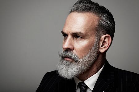 Retrato de detalle de hombre de negocios seus adulto llevaba traje de moda contra la pared vacía.