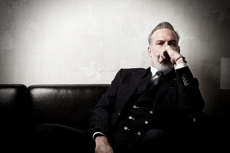 Retrato de hombre de negocios adulto que desgasta el juego de moda y moderna sentada en el sofá de cuero contra la pared vacía.