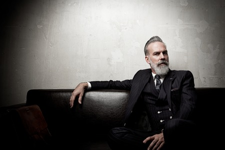 Portrait of adult businessman wearing trendy suit and sitting modern studio on leather sofa against the empty wall.
