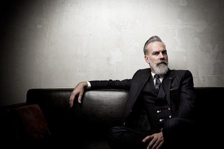 Retrato de hombre de negocios adulto que desgasta el juego de moda y moderna sentada en el sofá de cuero contra la pared vacía. Foto de archivo