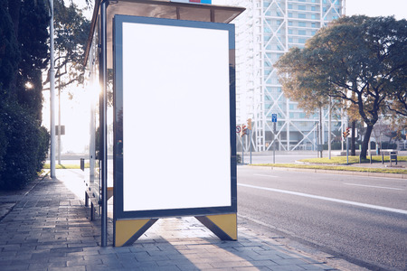 Photo blank lightbox on the bus stop in the modern city. Horizontal mockup Фото со стока