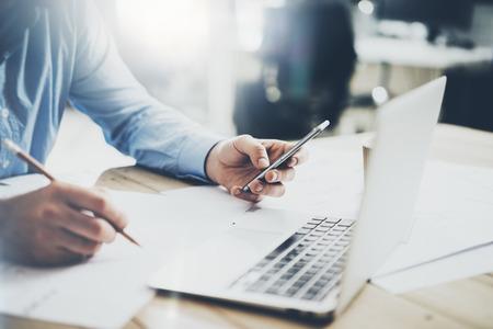 Geschäftsmann am Arbeitsplatz. Texting Nachricht Smartphone und hält Bleistift Hand. Generisches Design Notebook Holztisch. Horizontal Mockup,
