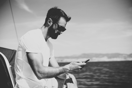 black male: Photo of young bearded man touching screen of smartphone on the yacht in sunny day. Horizontal mockup