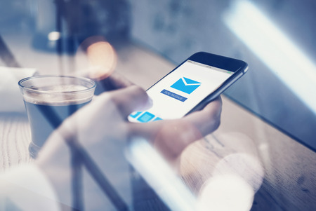 mobile sms: Close up of generic design smart phone holding in female hands for texting message. Sending message icon on screen. Cup coffee on the table. Stock Photo