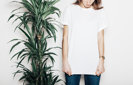 Young girl wearing blank t-shirt. Concrete wall background