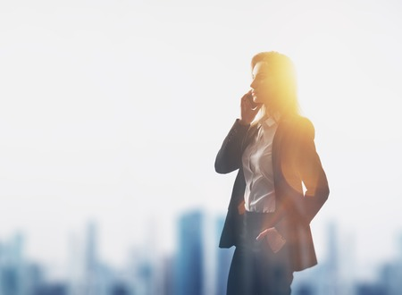 newsroom: Young woman wearing modern suit holding her smartphone in a hands. City on the background. Horizontal