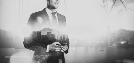 businessman suit: Photo of businessman holding smartphone. Double exposure photo of panoramic city view at sunrise. black white