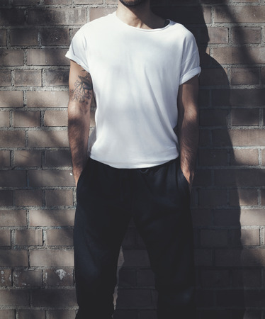 young guy: Bearded man with tattoo wearing blank white tshirt and black jeans. Bricks wall background. Horizontal