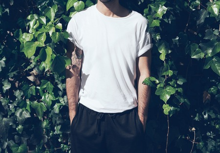 horizontal: Bearded man with tattoo wearing blank white tshirt and black sunglasses.Green garden wall background.
