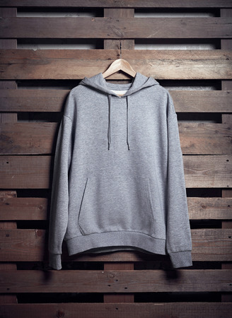 store sign: Photo of grey hoody hanging on wood background. Vertical