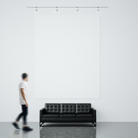 message board: Photo of man in gallery. Waching empty canvas hanging on the brick wall and generic design sofa wood floor.