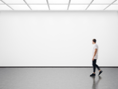 Photo of girl in modern gallery looking at the blank canvas. Horizontal Archivio Fotografico