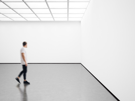 Photo of girl in modern gallery looking at the blank canvas. Horizontal Фото со стока