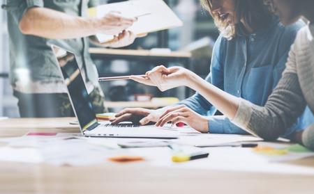 komunikacja: sukces zespołu. Photo młodych businessmans załoga pracuje z nowym projektem startowego. Generic projektowania notatnik na stole drewna. Analizowanie planów ręce klawiaturę.