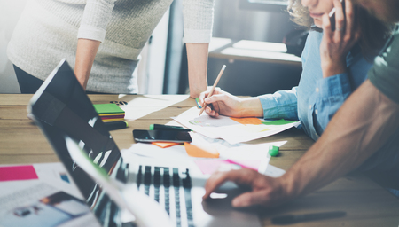 contabilidad: Contabilidad concepto de reunión de negocios. Foto El joven equipo de negocios que trabajan con el nuevo proyecto de inicio en el desván moderno. Genérico portátil de diseño en la mesa de madera, teléfono inteligente hablando
