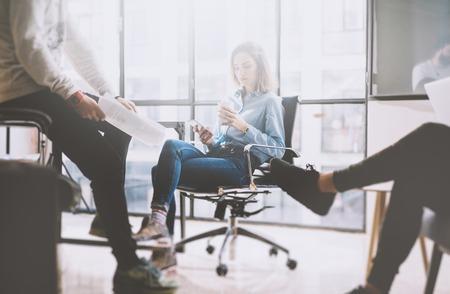 Teamwork-Konzept, Brainstorming. Geschäftsmann-Crew mit neuen Startprojekt in modernen Loft arbeiten. Frau hält Smartphone Hände.