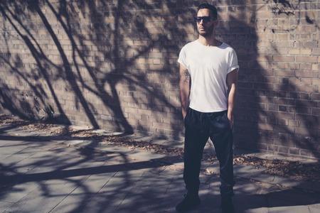 空白の白い t シャツを身に着けている刺青のひげを生やした男は。レンガ壁の前に立っています。街の背景 写真素材