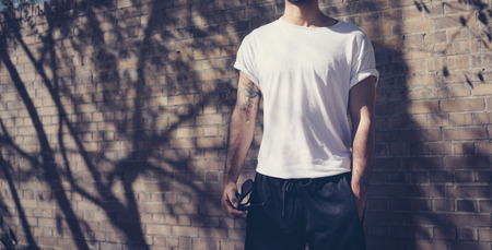 Photo man with tattoo wearing blank white tshirt, sunglasses. Stands in front of a brick wall. City street background. Wide mockup.