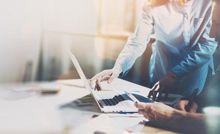 Team-Projekt. Foto junge Manager Talent mit neuen Startup-Projekt in der modernen Büro arbeiten. Generisches Design-Notebook auf Holz Tisch. Analysieren Pläne Hände, Tastatur.
