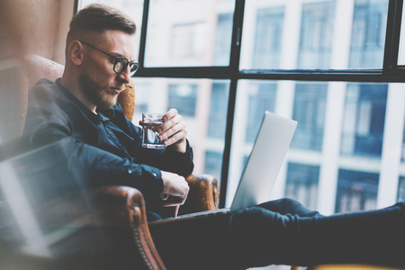 office manager: Bearded young businessman working on modern loft office. Man sitting in vintage chair. Using contemporary notebook, panoramic windows background.