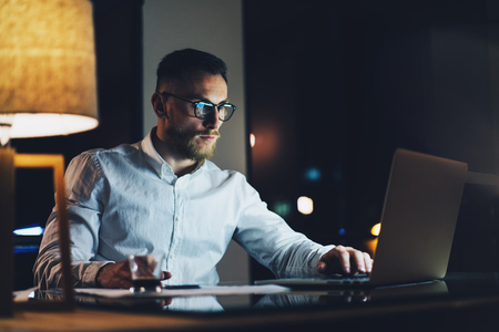 Bearded young businessman wearing white shirt working on modern loft office at night. Man using contemporary notebook texting message, blurred background.