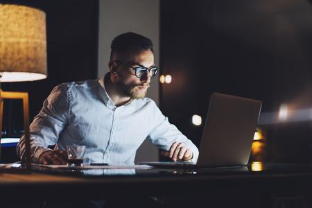 Bearded jeune homme d'affaires portant une chemise blanche travail sur le bureau de loft moderne dans la nuit. Homme utilisant un message SMS portable contemporain, arrière-plan flou.