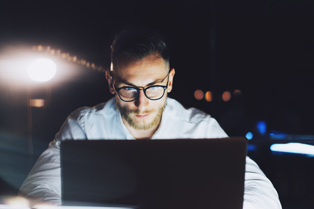 people on computers: Bearded businessman wearing glasses working on modern loft office at night. Man using contemporary notebook texting document, blurred background. Stock Photo