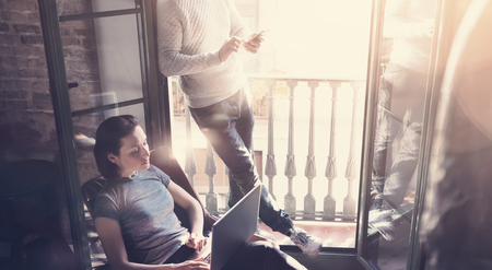 business lifestyle: Young couple work together. Photo woman and bearded man working with new startup project in modern loft. Using contemporary notebook, smartphone. Stock Photo