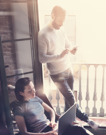 pareja joven de trabajo en conjunto. photo mujer y el hombre con barba de trabajo con el nuevo proyecto de inicio en el desván moderno. Usando el cuaderno contemporánea, teléfono inteligente. Vertical