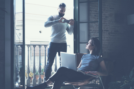 bloggers: Young couple work together. Bearded man making photo smartphone beautiful girl. Working with new startup project in modern loft. Using contemporary notebook. Stock Photo