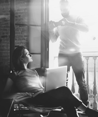 bloggers: Young couple together vacation. Bearded man making photo smartphone beautiful girl. Working with new freelance project in modern loft. Using contemporary notebook. Vertical, sunlight
