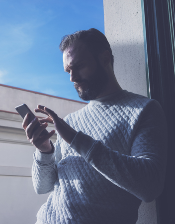 bloggers: Portrait bearded man touching screen mobile phone. Man using contemporary smartphone, blue sky background. Vertical