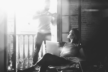bloggers: Young couple together vacation. Bearded man making photo smartphone beautiful girl. Working with new freelance project in modern loft. Using contemporary notebook. Horizontal, sunlight