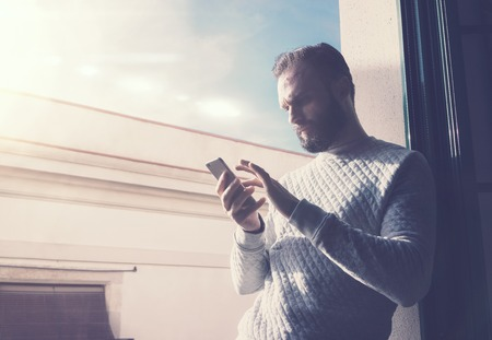bloggers: Portrait bearded man in modern loft. Man using contemporary smartphone, sunny sky background.