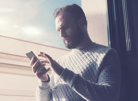 people   lifestyle: Portrait bearded man touching screen mobile phone. Man using contemporary smartphone, blue sky background. Horizontal Stock Photo