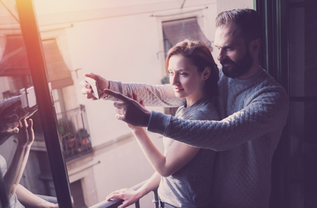 bloggers: Young couple summer holiday. Photo woman and bearded man making selfie smartphone in modern loft. Using contemporary smartphone. Horizontal, film effect.