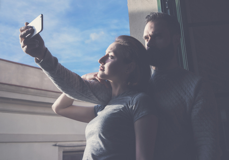 bloggers: Young couple summer holiday city. Photo woman and bearded man making selfie smartphone in modern loft. Using contemporary smartphone. Horizontal, film effect.