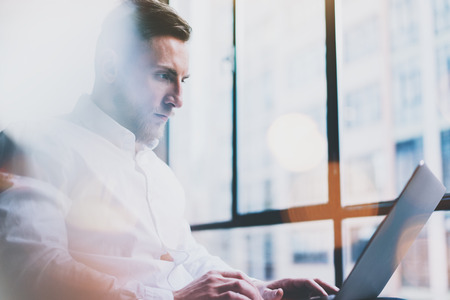 computer room: Bearded young businessman working on modern loft office. Man wearing white shirt and using contemporary laptop. Panoramic windows background. Stock Photo